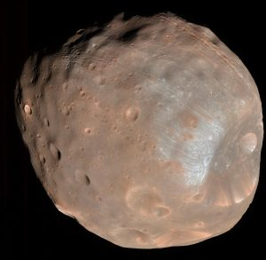 Oval-shaped pinkish rocky moon with many mostly small craters.