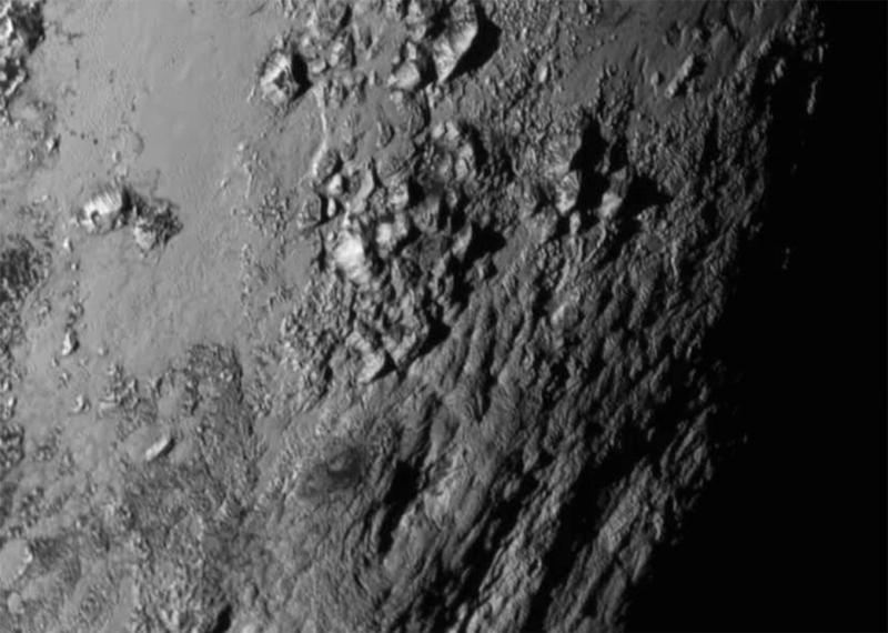 Pluto's rugged, irregular mountainous terrain in black and white from space.