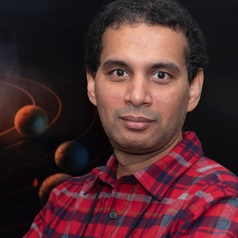 Smiling man in checkered shirt, with two planets behind him.
