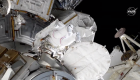 Astronaut in spacesuit outside a large, complicated spacecraft.