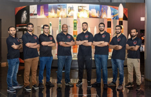 A team of men, mostly in blue jeans and polo shirts, standing in front of a display.