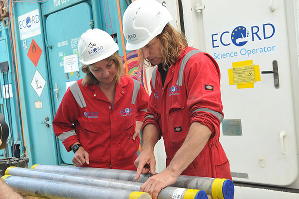 Two people in hard hats and orange jumpsuits look at long gray cylinders.