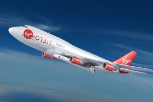 An artist's illustration of red and white plane displaying the Virgin Orbit logo is drawn carrying the smaller LauncherOne vehicle into a blue sky.