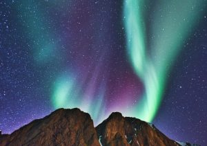 Green curtains of an aurora in a deep blue starry sky over a rocky hilltop.