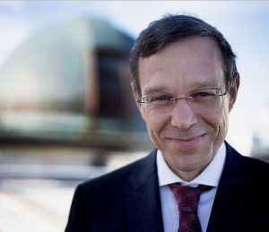 A smiling middle-aged man in suit and tie, with a telescope dome in the background.