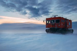 Big red box-like vehicle on treads crossing a vast snowy area.