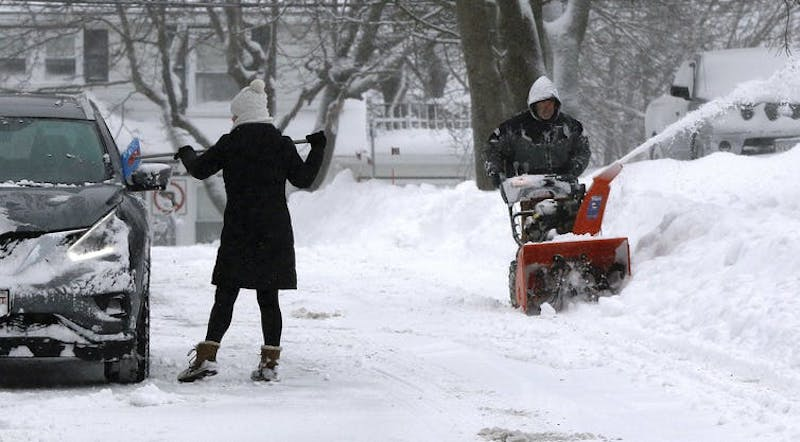 A person scraping snow off a car and a person pushing a snowblower.
