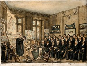 Antique etching of class watching a man in academic robe holding up a rock.