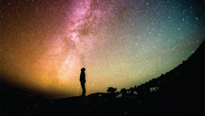 A human standing under the Milky Way in starry sky, looking up.