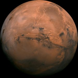 A nearly full reddish Mars seen from orbit, with a giant dark slash covering near a whole hemisphere.