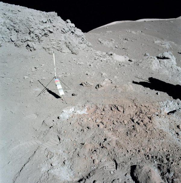 Gray barren landscape, with slightly orange area and small scientific instrument.