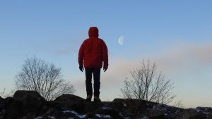 A man in a parka, standing on a hilltop, facing away from the camera, toward a half moon in the sky.