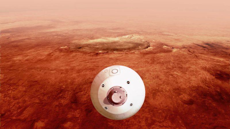 Mars'ın kırmızımsı bir manzarası üzerinde dönen bir uzay kapsülünün üstten görünümü.