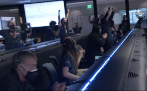 Flight engineers in a control room leaping up, waving their arms and cheering.