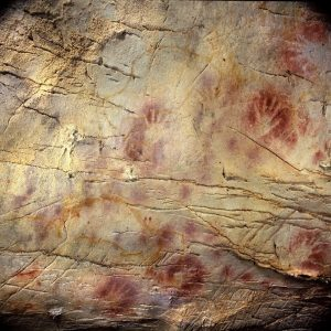 Handprints surrounded by red, like a stencil, on a cracked, brown rock wall.