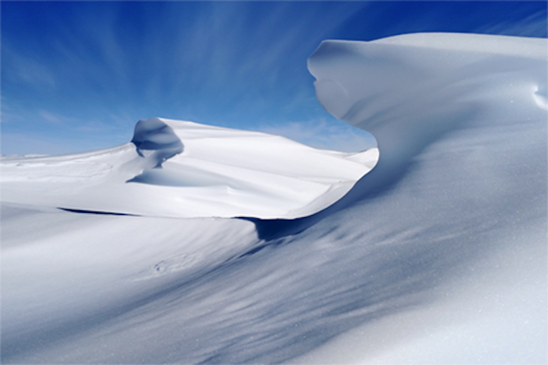 Angular hills of snow similar to dunes against a blue sky.