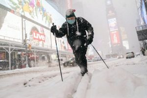 A person skiing in the snow on a city street.