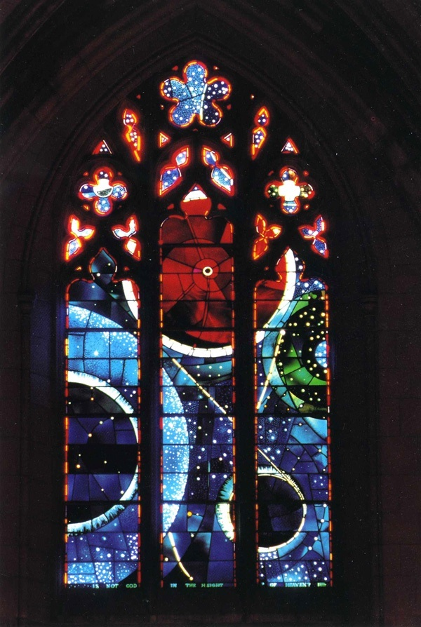 Tall stained glass window with colored circles and pointed arch top.