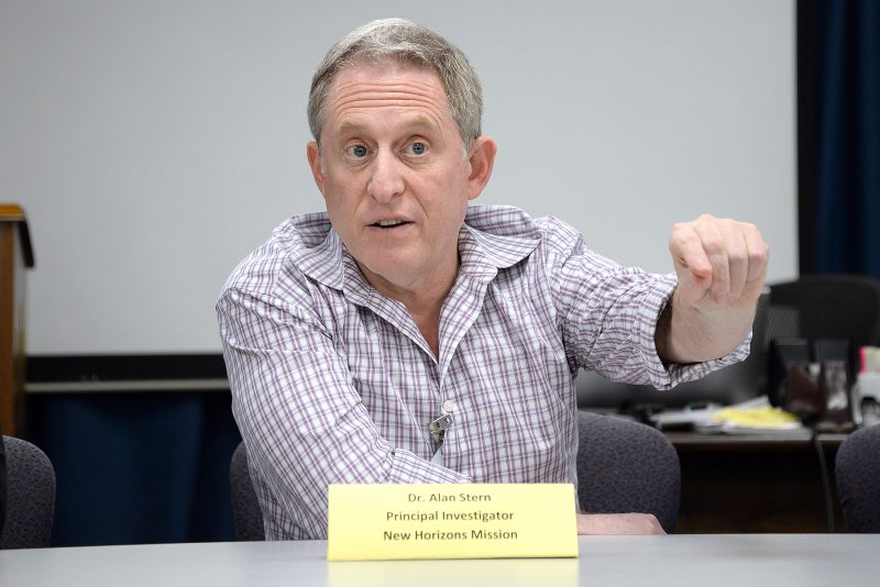 Man sitting at table pointing toward audience.