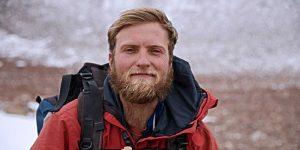 Man with sandy beard in parka.