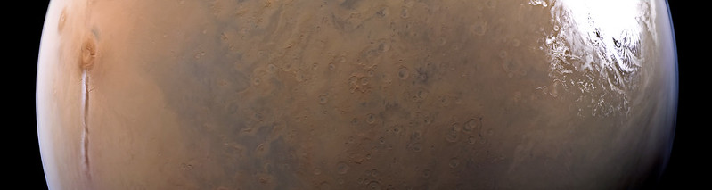 Horizontal slice of Mars with long thin cloud on right and large white patch on right.