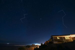 Night sky with stars and drawn lines for Cassiopeia and the Big Dipper.