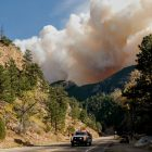 Smoke from a wildfire behind mountains, truck on road in foreground.
