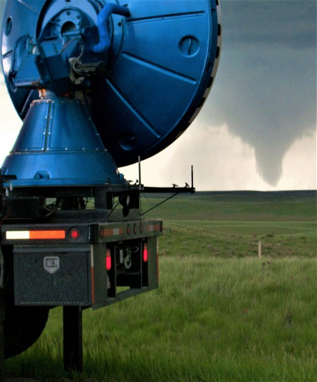 Bright blue vertical radar dish in foreground, tornado in background.