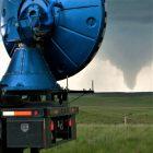 Radar dish in foreground. tornado in background.