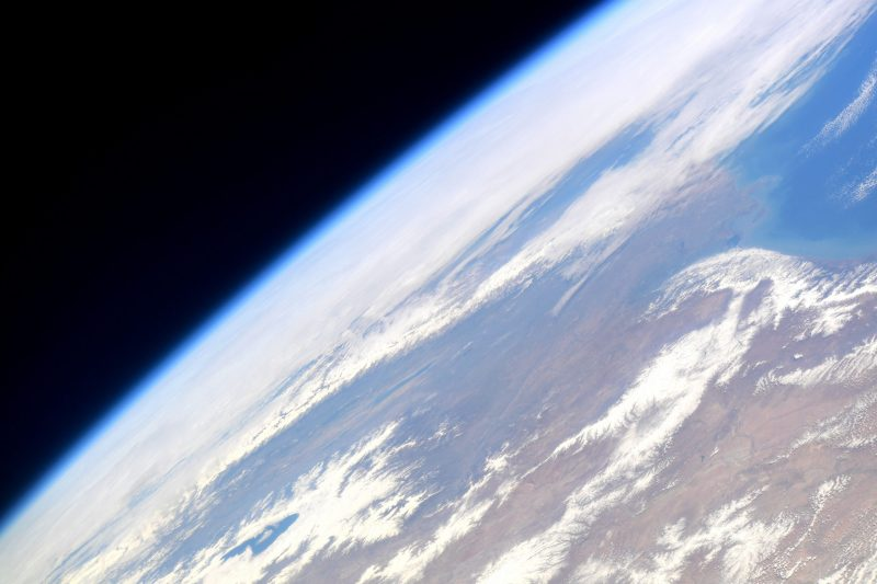 Partial view of Earth from orbit with clouds and fuzzy atmosphere visible aganist black space.