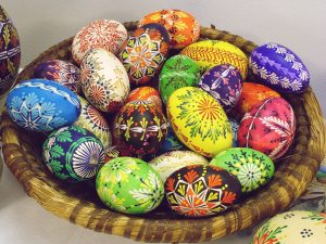 Basket of eggs with brightly colored, intricate designs painted on them.