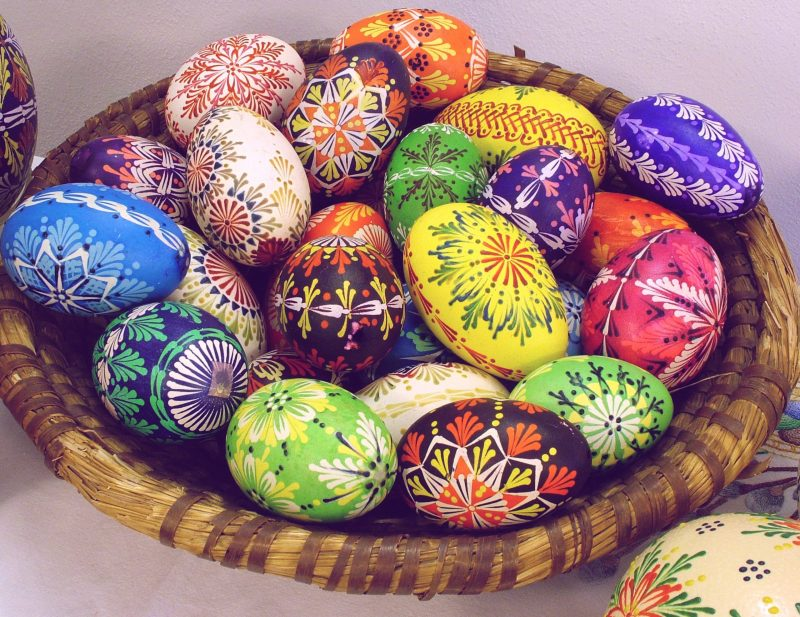 Basket of eggs intricately painted in many bright colors.