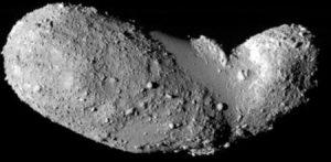 Long gray rocky object on black background.