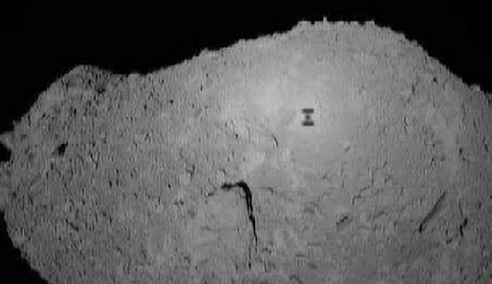 Rocky gray object with tiny barbell-like shadow on its surface.