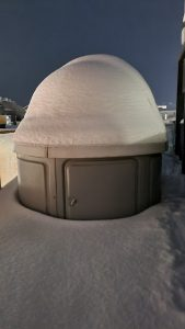 Heavily snowcapped observatory in the shape of a beige cylinder.