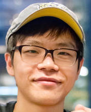 Smiling young man with eyeglasses and cap on head.