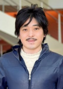 Man with black hair and thin mustache wearing blue zip-up jacket.