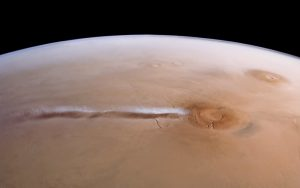 White cloud streams out from side of reddish circle on Mars.