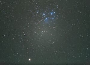 Orange light near bottom, blue stars and haze at top.