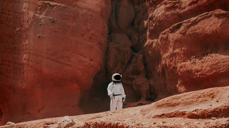 Person in white space suit walks among red rocky landscape.