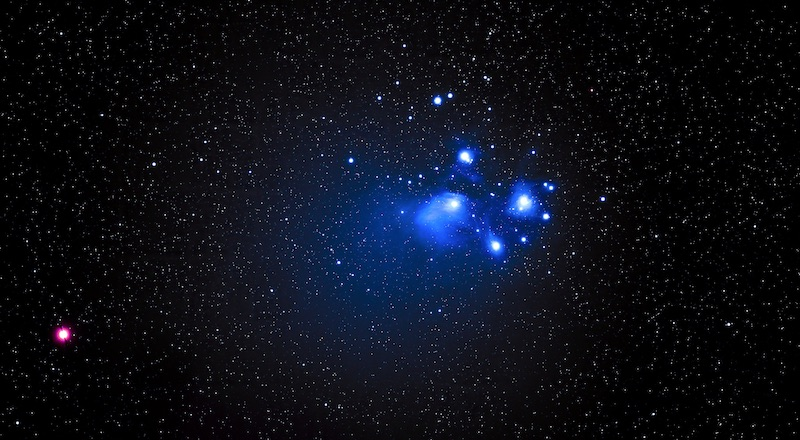 Bright red star-like light to the far left and bright blue stars with shining blue wisps (gas) near center right.