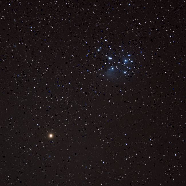 Red bright dot (Mars) at bottom left, blue star cluster (Pleiades) at top right, on black background.
