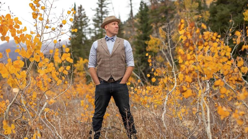 Man with hat, vest and bow tie stands by trees with yellow leaves.