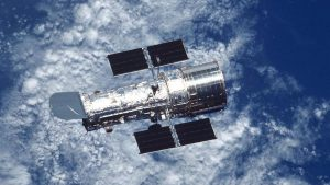 A cylinder-shaped, silver spacecraft is pictured floating above the blue and cloud-covered surface of Earth.