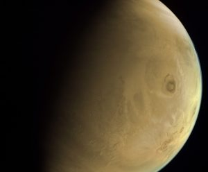 Close-up of the surface of Mars, in a beige hue. One large dark spot to the right in the image, Olympus Mons, and 3 other spots to its right, which are its sister volcanoes.