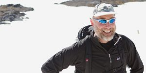 Bearded man in sunglasses smiling and standing on ice.