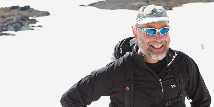 Bearded man in winter garbe and sunglasses smiling and standing on ice.