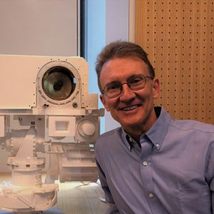 Smiling man standing next to tall robotic instrument with a big lense.