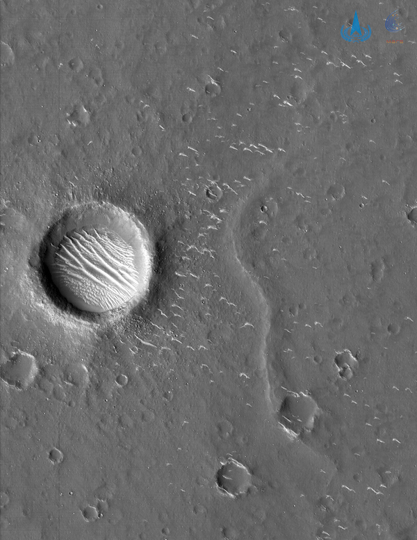 Greyscale image with a crater containing dunes to the left/center, a few other smaller craters and a winding ridge.