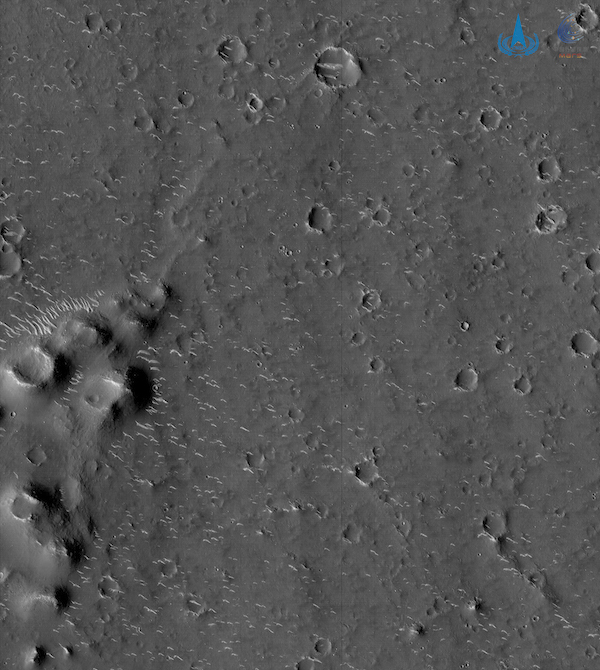 Grayscale image of a planet surface, with small craters and a hilly area on the left side.